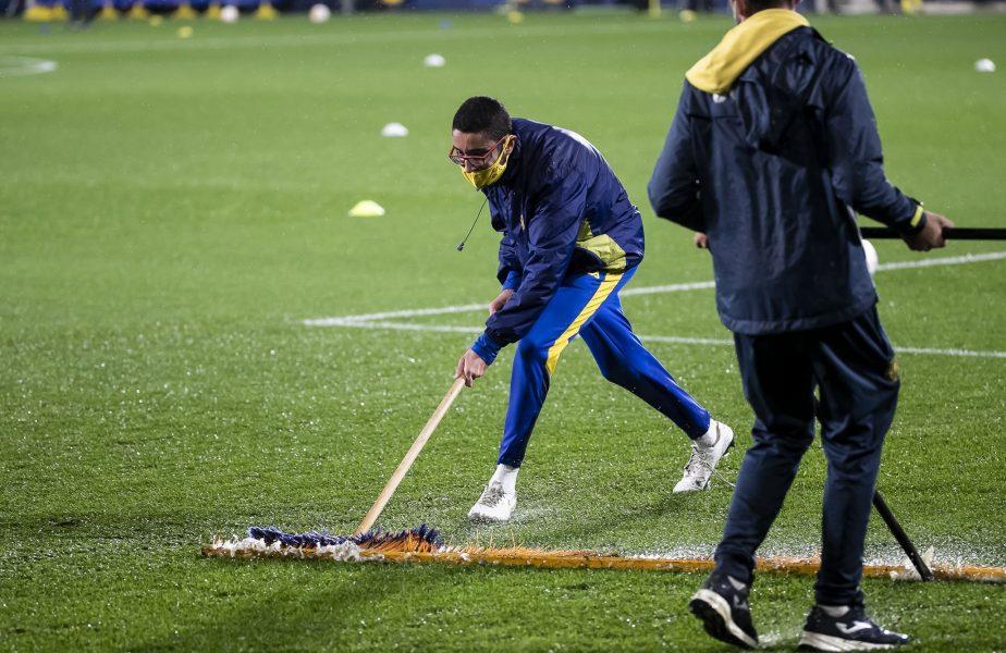 Staff-ul de la Villarreal lucrând să dea apa de pe terenul de fotbal